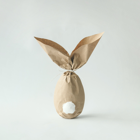 Easter bunny paper gift egg wrapping diy idea. Minimal easter concept Banco de Imagens
