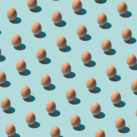パターンはパステル調の青の背景に卵から成っています。最小限の食べ物のコンセプトです。