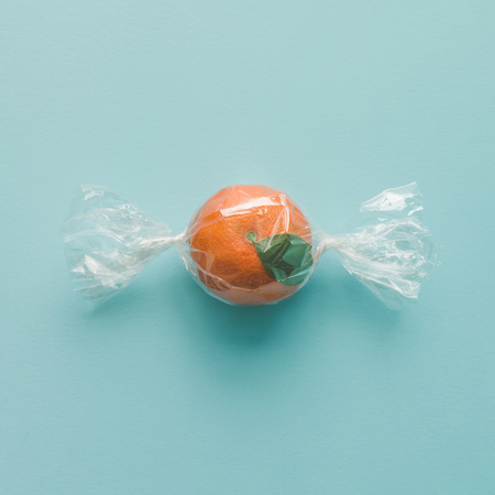 Arancio avvolto come caramelle su sfondo blu brillante. concetto di cibo minimo. Archivio Fotografico - 73764487
