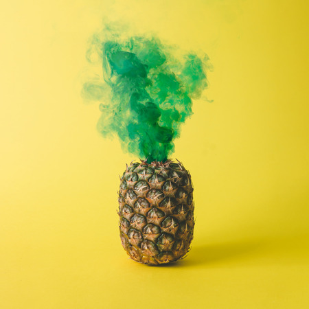 Pineapple with green smoke on bright yellow background. Friut concept. Stock Photo