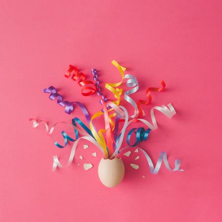 ピンクの背景に党吹流しと卵します。イースターのコンセプトです。フラットが横たわっていた。