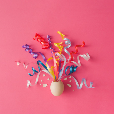 minimal: Egg with party streamers on pink background. Easter concept. Flat lay. Stock Photo
