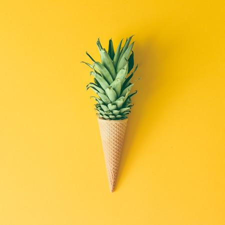 Cono di gelato con foglie di ananas su sfondo giallo brillante. Concetto di frutta e caramelle. Pianta piatta. Archivio Fotografico - 74236951