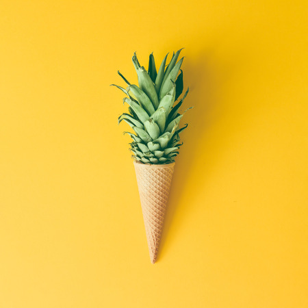 Ice cream cone with pineapple leaves on bright yellow background. Fruit and candy concept. Flat lay. Stock fotó - 74236951
