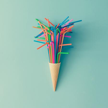 Roomijskegel met kleurrijk het drinken stro op heldere blauwe achtergrond. Minimaal voedselconcept. Plat leggen. Stockfoto