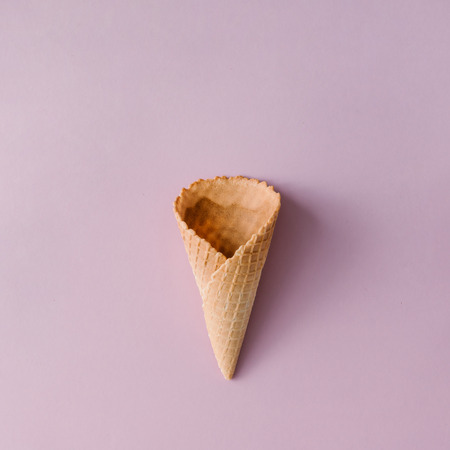 Ice cream cone on pastel pink background. Minimal summer concept. Flat lay.