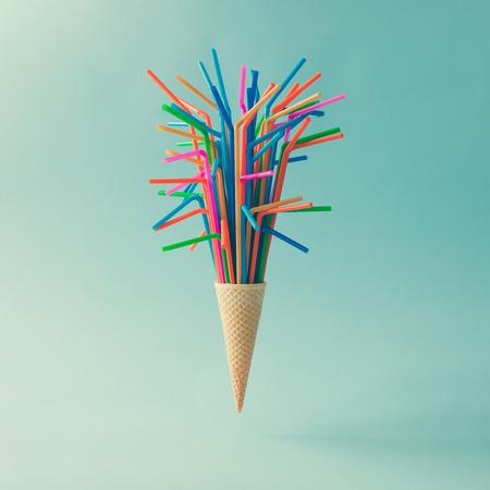 밝은 파란색 배경에 마시는 빨 대와 함께 아이스크림 콘. 최소한의 음식 개념.