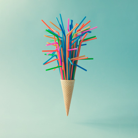 Ice cream cone with colorful drinking straws on bright blue background. Minimal food concept.