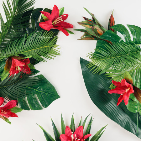 Creative layout made of tropical palm leaves and colorful flowers. Summer concept. Flat lay.