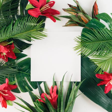 Creatieve lay-out gemaakt van tropische palmbladeren en kleurrijke bloemen. Zomerconcept. Vlak liggen.