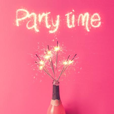 Garrafa de champagne com sparklers em fundo rosa. Leito plano.