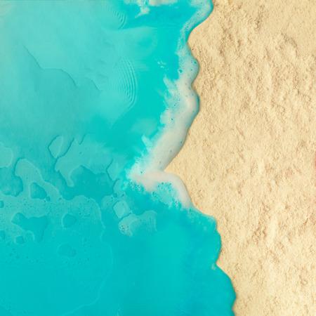 Concetto minimale creativo della spiaggia. Disposizione di vacanza estiva con acqua blu e sabbia su sfondo luminoso. Pianta piatta.