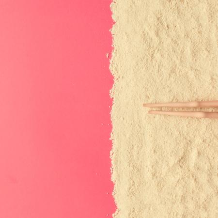 Concetto minimale creativo della spiaggia. Paesaggio estivo con gambe bambole su sfondo rosa. Pianta piatta.