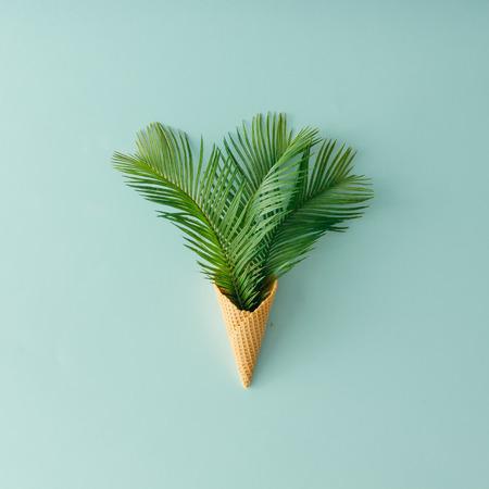 Hojas de la palmera en cono de helado en fondo azul pastel. Piso tumbado. Verano tropical concepto.