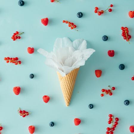 Flor branca no cone de sorvete com padrão de fruta da floresta. Leito plano. Conceito de verão.