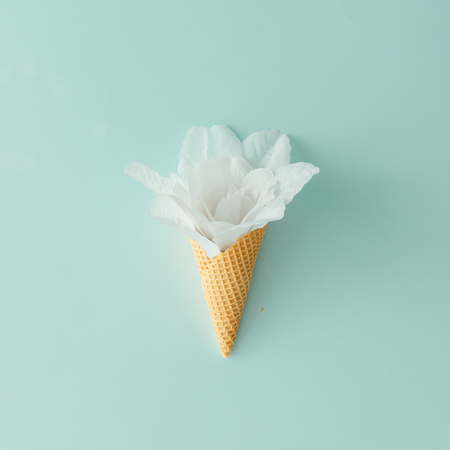 White flower in ice cream cone on pastel blue background. Flat lay. Summer tropical concept.
