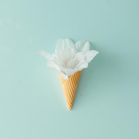 Fiore bianco in cono di gelato su sfondo blu pastello. Pianta piatta. Concetto tropicale estivo.