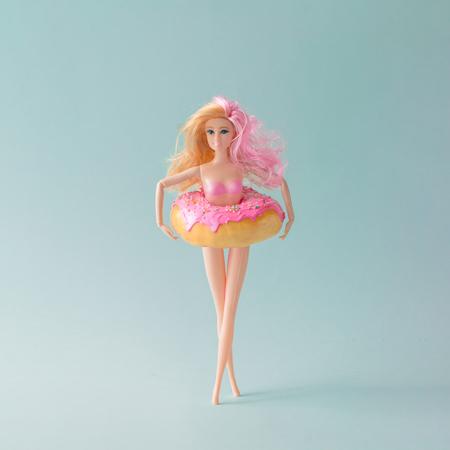 ピンク ドーナツと女の子の人形は、ブルーのパステル調の背景にリングを泳ぐ。創造的な夏のコンセプトです。