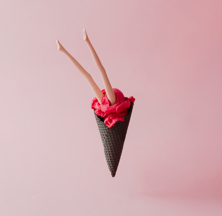 Doll legs in red ice cream with black cone on pink pastel background. Creative summer concept.