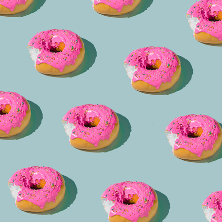 Rosa glasierte Donut Muster auf blauem Pastell Hintergrund. Kreatives Konzept.