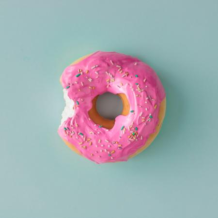 블루 파스텔 배경에 핑크 유약 도넛입니다. 평평한 평신도. 창조적 인 개념입니다. 스톡 콘텐츠