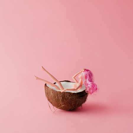Doll with pink hair bathing in coconut. Summer concept.