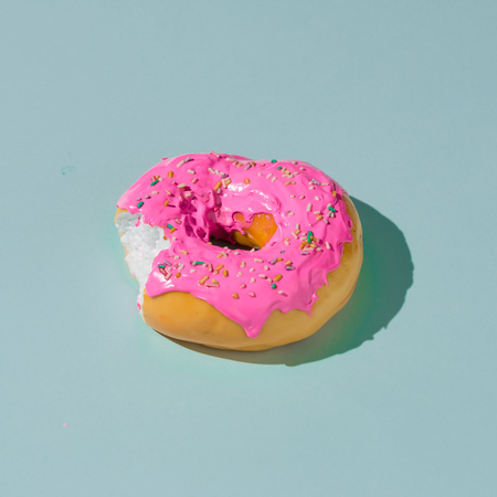 Pink glazed donut on blue pastel background. Creative concept. Stock Photo