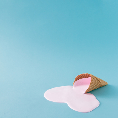 Pink ice cream spilled on pastel blue background. Minimalistic summer food concept. Stock Photo