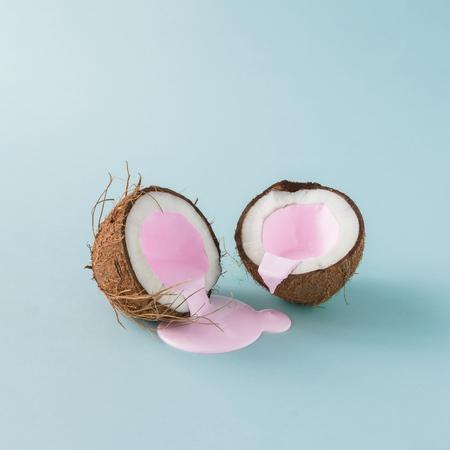 Noix de coco craqué en deux avec du lait rose versé. Minimalisme. Concept créatif alimentaire.