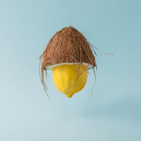 Zitrone mit Kokosnuss Hut auf Pastell blauem Hintergrund. Lustiges Essen kreatives Konzept.