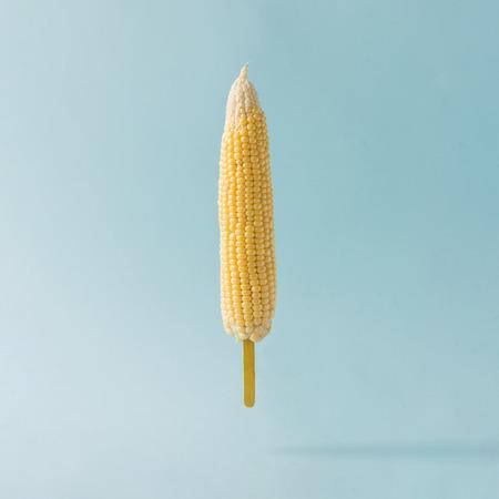Kool maïs met ijs stok op pastel blauwe achtergrond. Voedsel creatief concept.