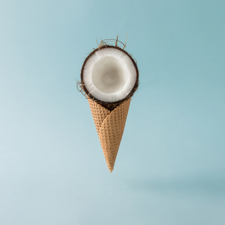 Coconut with ice cream cone on pastel blue background. Foos creative concept. Imagens