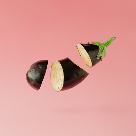 Eggplant sliced on pastel pink background. Minimal fruit concept.
