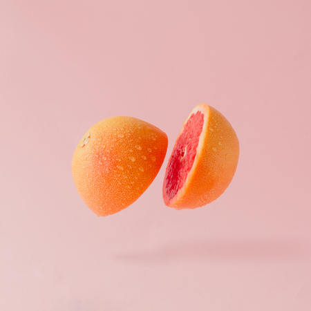 グレープ フルーツは、パステル ピンクの背景でスライスされました。最小限の果物概念。