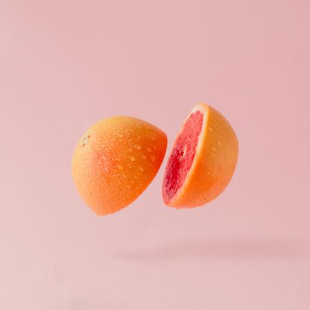 在粉紅色的背景上切的葡萄柚。最小的水果概念。
