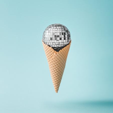 밝은 파란색 배경에 디스코 공 아이스크림. 최소한의 파티 개념. 스톡 콘텐츠