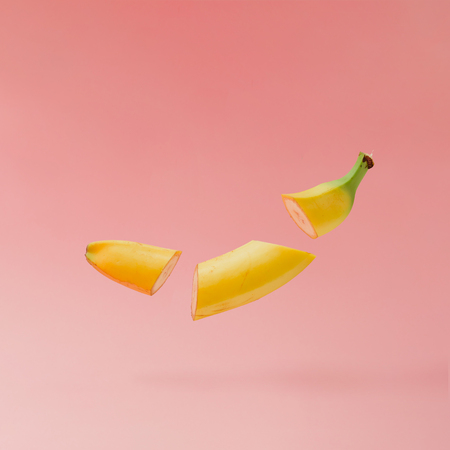 Banana sliced on pastel pink background. Minimal fruit concept. Imagens