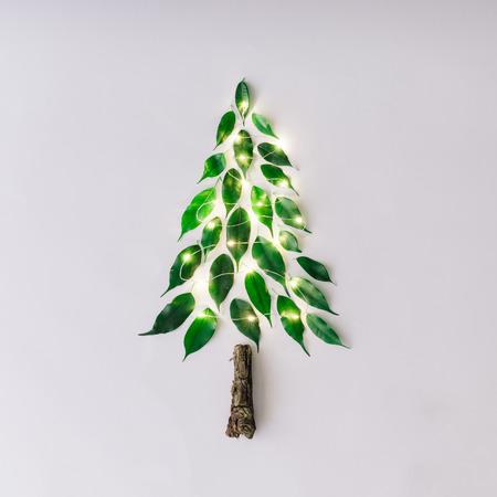 Árvore de Natal feita de folhas e galho. Leito plano. Conceito mínimo de natureza do Ano Novo.