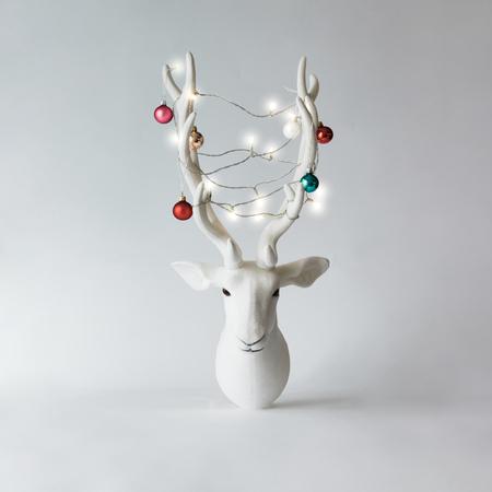 Cabeza de renos de Navidad blanca con astas con adornos de Navidad y luces. Concepto de año nuevo.
