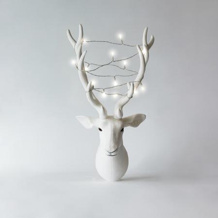 Biała Bożenarodzeniowa renifer głowa z poroże z bożonarodzeniowe światła. Koncepcja nowego roku.