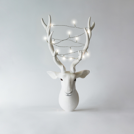 White Christmas reindeer head with antlers with christmas lights. New Year concept.