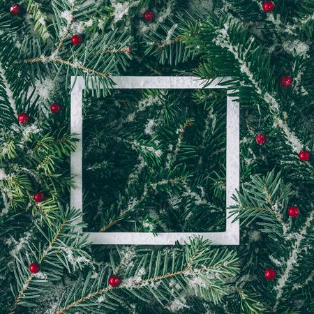 Layout creativo fatto di rami di albero di Natale con la neve e carta nota di carta. Distesi. Concetto di natura nuovo anno.
