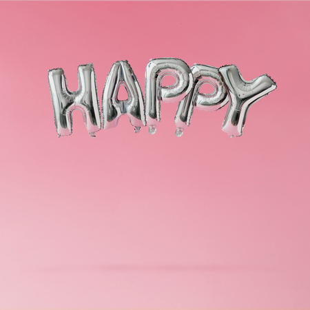Счастливый баллоны, плавающие на фоне розового пастель. Концепция праздника.