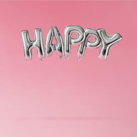 Globos felices flotando en el fondo de color rosa pastel. Concepto de celebración