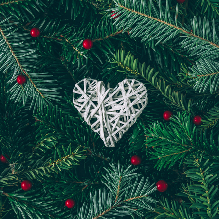 Creative layout made of Christmas tree branches with heart decoration. Flat lay. Nature New Year concept.