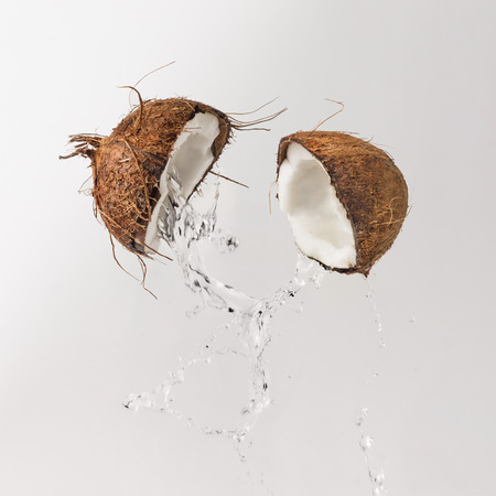 Cracked coconut with water splash. Summer tropical concept.
