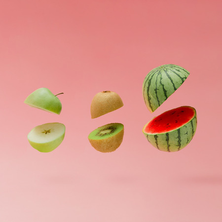 Watermelon, apple and kiwi sliced on pastel pink background. Minimal fruit concept. Reklamní fotografie