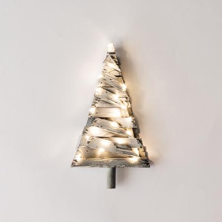Árbol de Navidad minimalista con luces sobre fondo brillante. Concepto mínimo de la naturaleza de año nuevo.