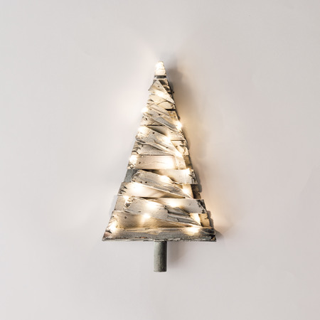 Minimalistic Christmas tree with lights on bright background. New Year nature minimal concept.