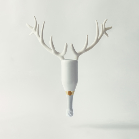 White Champagne bottle with reindeer antlers on bright background. New year party concept. Stock Photo